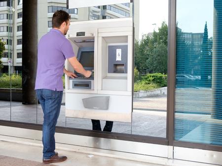 Mann mit seiner Kreditkarte in einem ATM für Bargeldabhebung Lizenzfreie Bilder