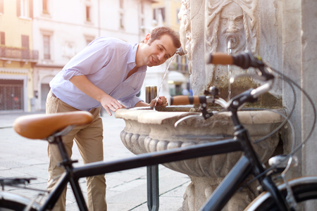 townhouses: Man is resting next to his bike in the city street Stock Photo