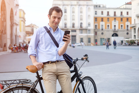 townhouses: Man standing next to his bike hand holding mobile telephone