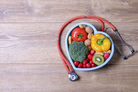 Heart shaped dish with vegetables and stethoscope isolated on wooden background
