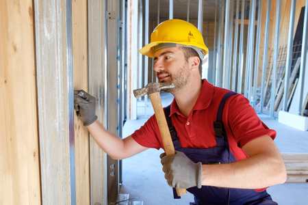 pounding head: Carpenter using hammer in a construction site Stock Photo
