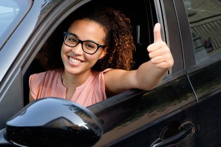 幸せな若い女性は、彼女の新しい車に装着されています。