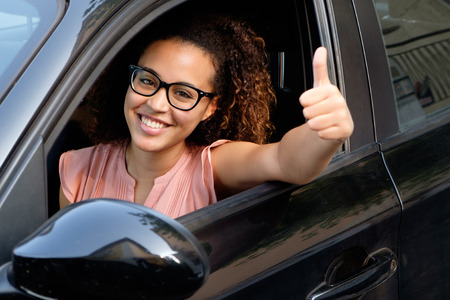 행복한 젊은 여자가 그녀의 새 차에 앉아 스톡 콘텐츠