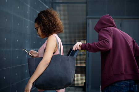 Thief stealing the wallet from the bag of a distracted woman