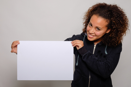 displaying: Black woman displaying white banner isolated on background Stock Photo