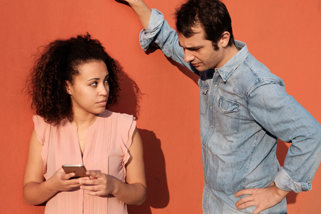 distrustful: Man spying the mobile phone of her girlfriend