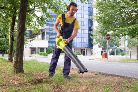 hobbyist: Gardener using his leaves blower in the garden