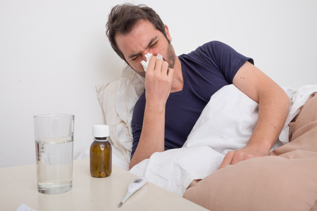 common room: Man feeling bad lying in the bed and blowing his nose Stock Photo