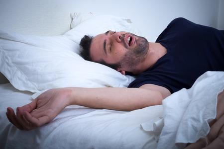 cansancio: Hombre que duerme en su cama y roncando Foto de archivo