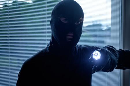 malefactor: Burglar wearing a balaclava holding a flashlight