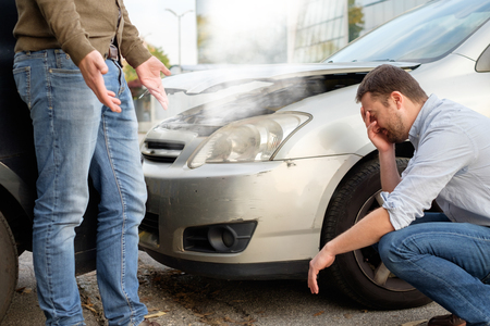 rear end: Two men arguing after a car accident on the road