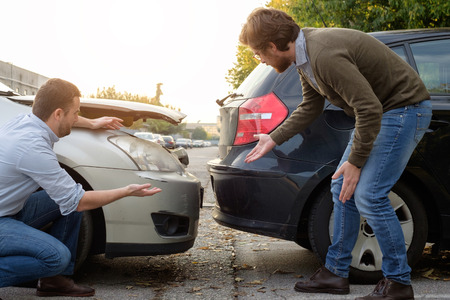 Dos hombres discuten después de un accidente de tráfico en la carretera