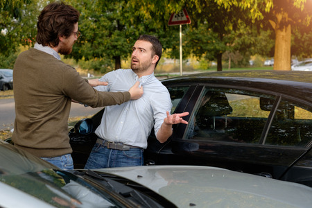 fender bender: Two men arguing after a car accident on the road