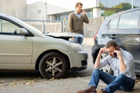 Two men calling car help assistance after an accident