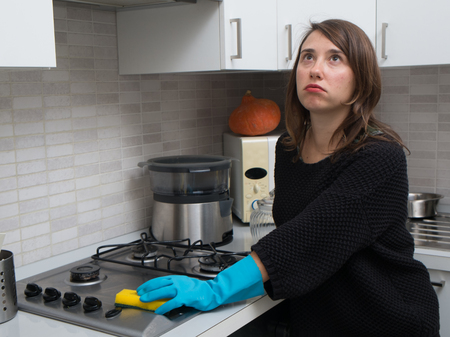 bored woman: Bored woman cleaning stainless steel gas surface in  the kitchen at home Stock Photo