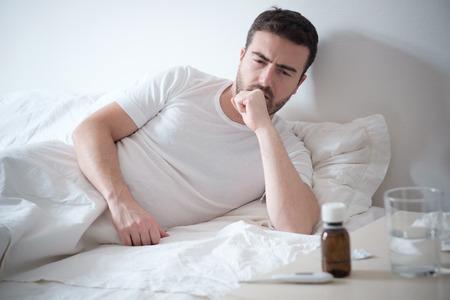 El hombre que se siente mal acostado en la cama y tos Foto de archivo