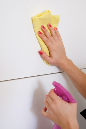 Woman cleaning white surface in  the kitchen at home