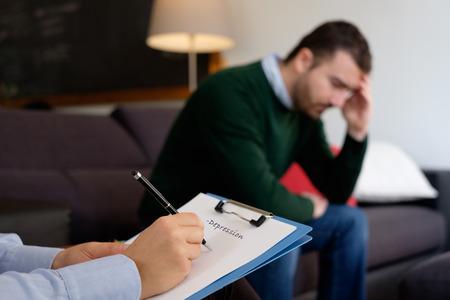 Hombre con problemas de salud mental en el estudio psiquiatra Foto de archivo