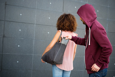 looting: Thief stealing the wallet from the bag of a distracted woman