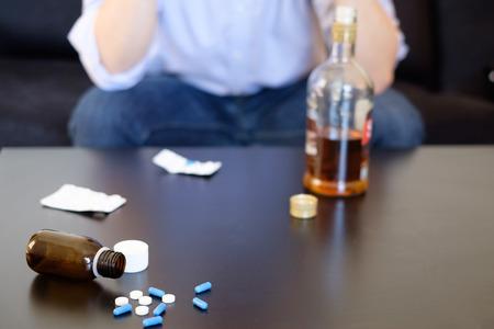 Depressieve man het mengen van alcohol en pillen Stockfoto