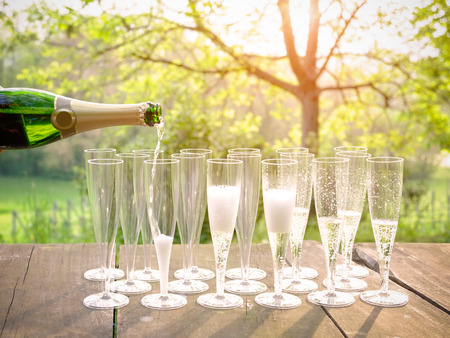 Hand pouring wine into flute glasses of champagne