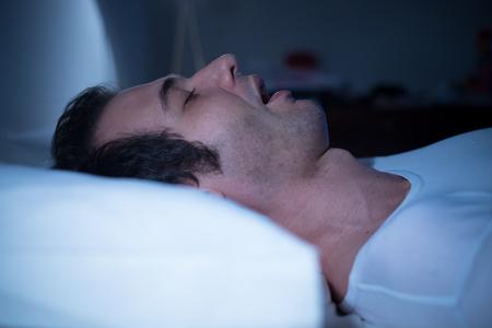 남자는 밤에 그의 침대에서 자고있다.