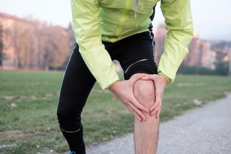 Runner mit verletzten Knöchel beim Training im Stadtpark in der kalten Jahreszeit
