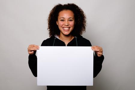 黒人女性の背景に分離された白のバナーを表示します。