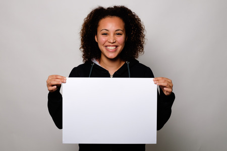 Black woman displaying white banner isolated on background Imagens