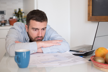 unpaid: Frustrated man calculating bills and tax  expenses