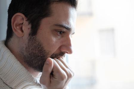 Ritratto triste dell'uomo che osserva fuori dalla finestra