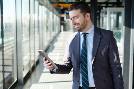 businessman waiting call: Businessman is looking at his mobile phone while is going to work Stock Photo