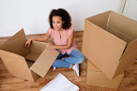 Happy woman surrounded by large boxes ready for home relocation Stock Photo