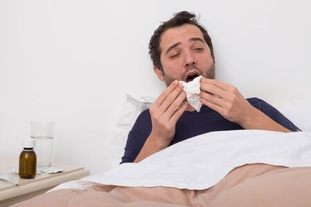sleeping pills: Man feeling bad lying in the bed and blowing his nose Stock Photo