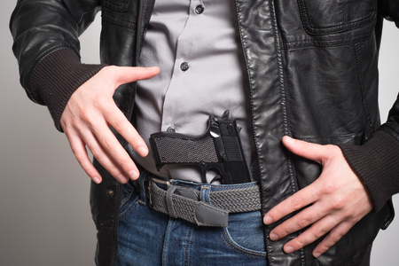 concealed: Man pulling out a gun ready to shoot