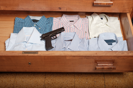household accident: Gun hidden in a drawer full of shirt at home Stock Photo