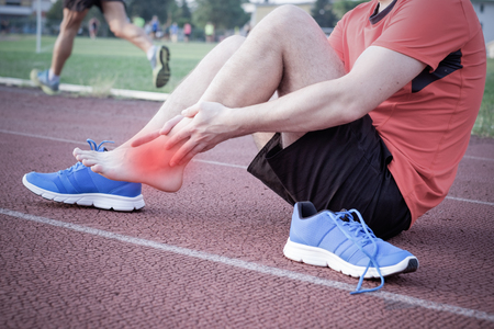 Runner with injured ankle on the track Archivio Fotografico
