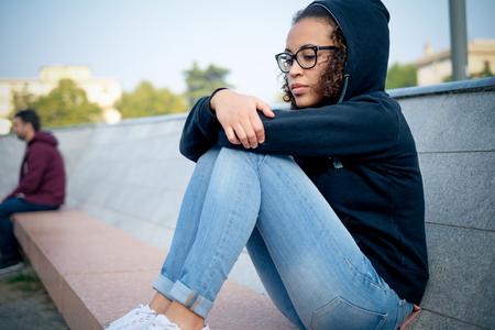 Droevige jonge Afro-Amerikaanse meisje alleen in de stad straat