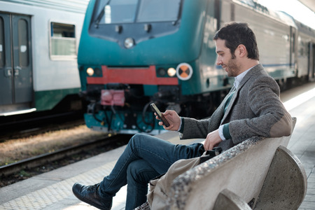 businessman waiting call: man waiting for the train seated in a train station platform
