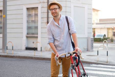 Fashionable man holding his bike in the city street