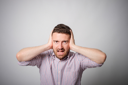Man with hands on ears bothered annoyed