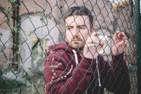 Sad and troubled boy under metal fence