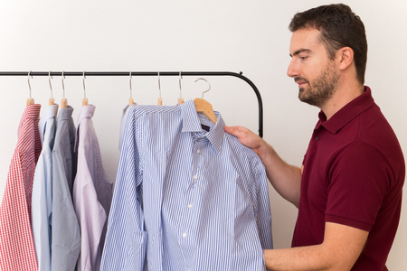 tailored: Man choosing shirts in several colors and textures