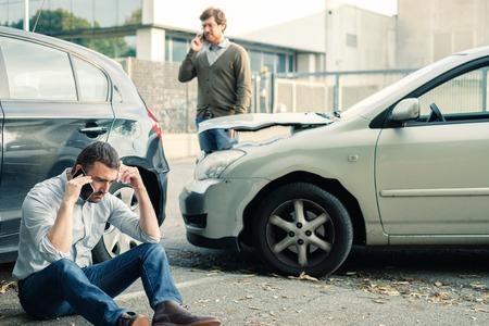 fender bender: Two men calling car help assistance after an accident