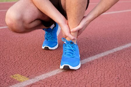 contracture: Runner with injured ankle on the track Stock Photo