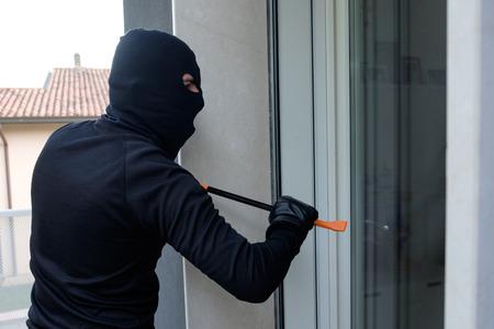 malefactor: Burglar trying to force a window lock using a crowbar Stock Photo
