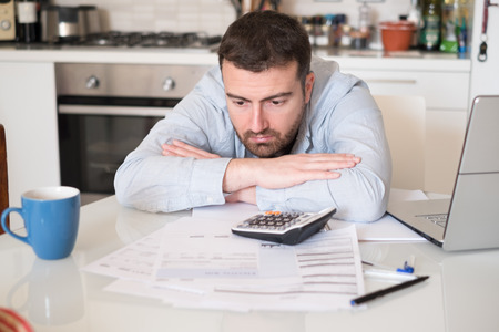 Frustrated man calculating bills and tax  expenses Stok Fotoğraf - 74007209