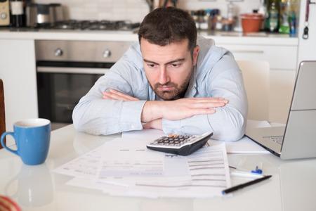 Gefrustreerd man berekenen rekeningen en fiscale uitgaven Stockfoto