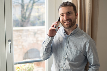 house call: Man talking using his mobile phone at home