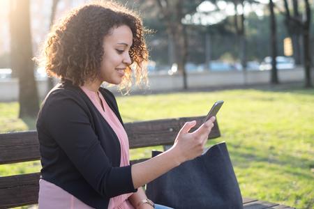 Zwarte die app op mobiele telefoon in het stadspark gebruiken